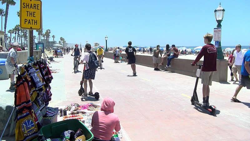 Scooters and bikes riders on the Mission Beach Boardwalk, July 1, 2019.
