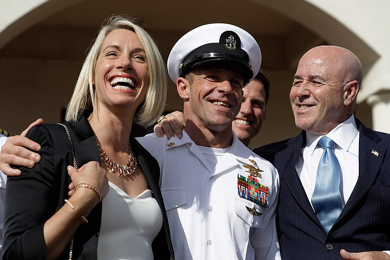 Navy Special Operations Chief Edward Gallagher, center, walks with his wife, ...