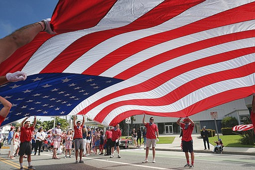Participants carry an American flag during the 4th of July parade in Santa Mo...