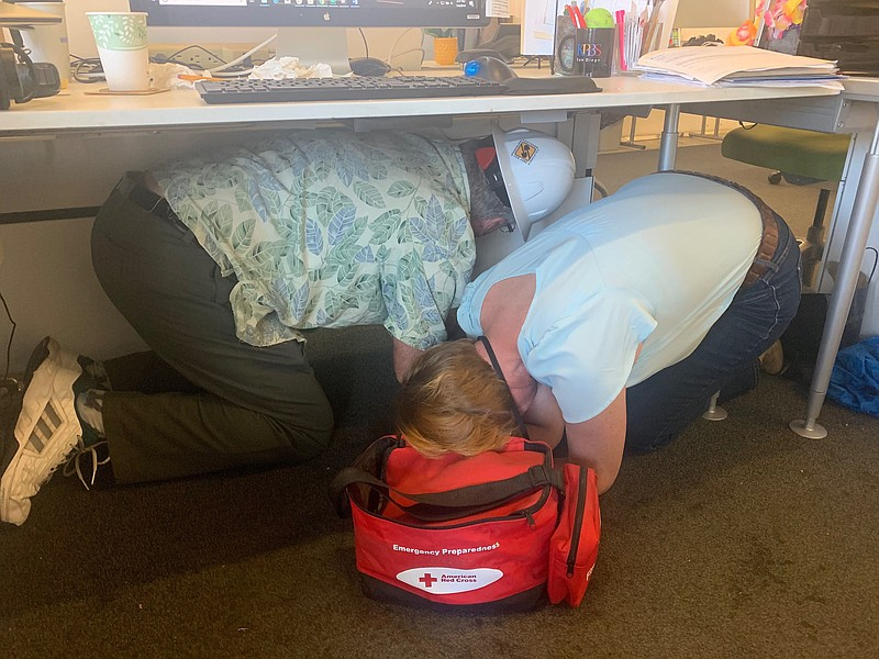 Employees at KPBS practice taking cover under a desk, July 4, 2019.