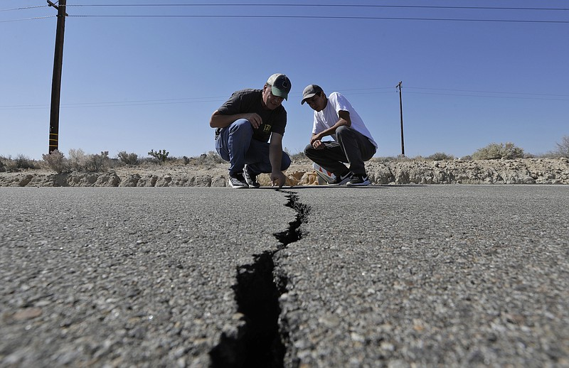 Ron Mikulaco, left, and his nephew, Brad Fernandez, examine a crack caused by...