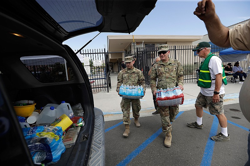 Members of the National Guard load water onto an SUV in the aftermath of an e...