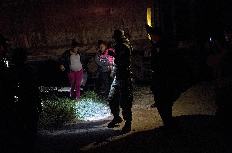 A Mexican immigration agent and police detain migrants during a raid on the c...