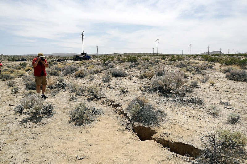 A visitor takes a photo of a crack on the ground following recent earthquakes...
