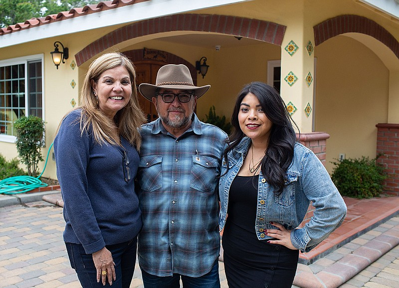 Helen, Juan, and Monica Rivera in front of Juan and Helen's home, on May 26, ...
