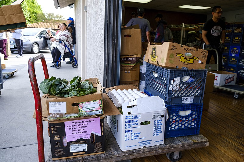 A cart loaded with fresh vegetables, eggs, and milk at the Downey food bank i...