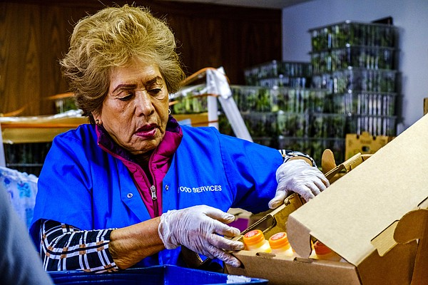 Elvira Rodriguez, a volunteer at the food bank, unpacks a...