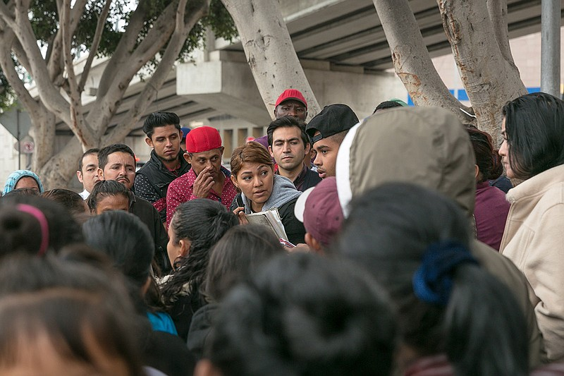 A crowd of asylum seekers gather around a waitlist for entering the U.S. thro...