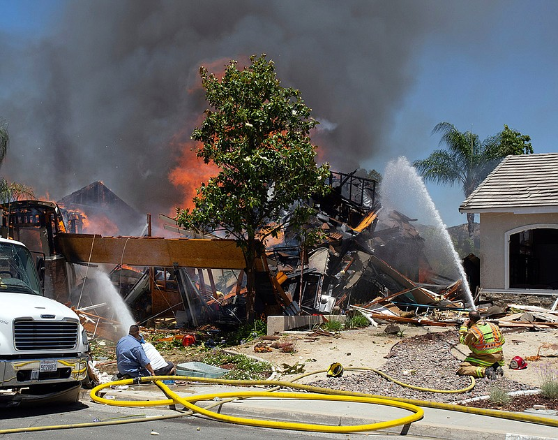 A firefighter and civilians train fire hoses on a burning home after an explo...