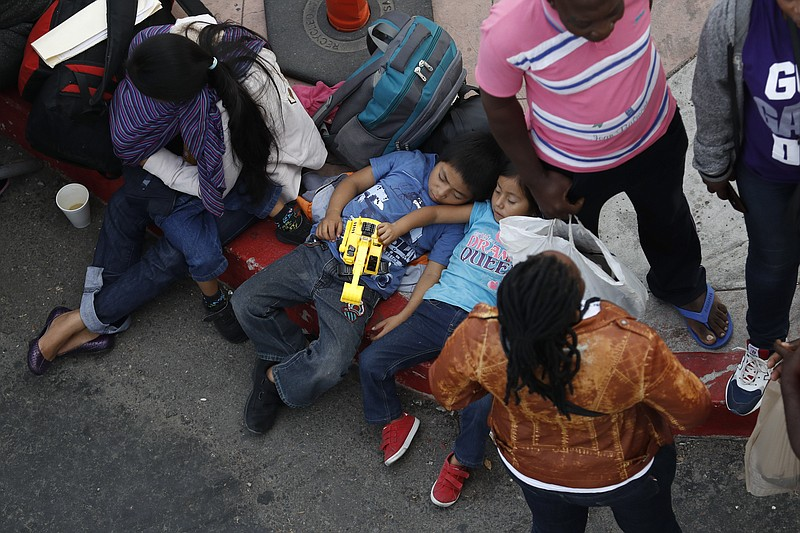 People wait to apply for asylum in the United States along the border, Tuesda...