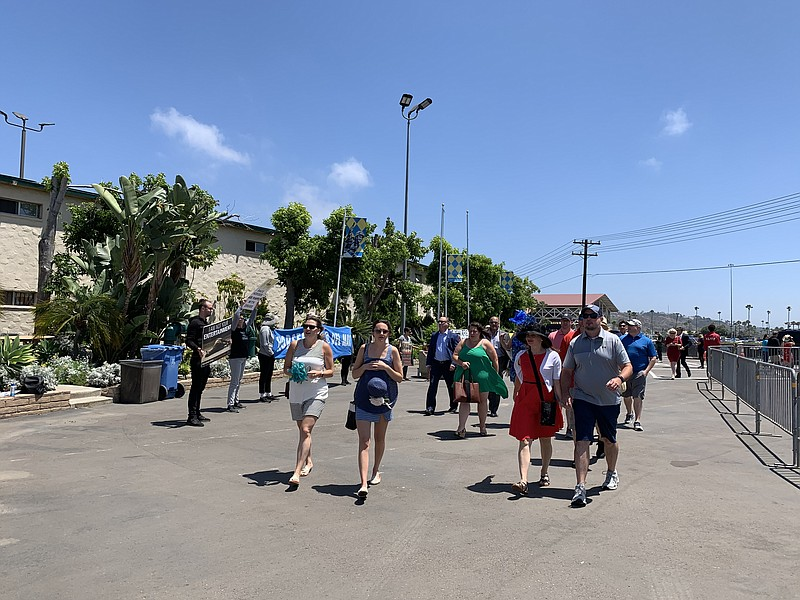 People arrive for Opening Day at the Del Mar Fair Grounds as demonstrators pr...