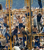 The crowd and people sitting on the sound tower. Bethel, N.Y., Aug. 1969.