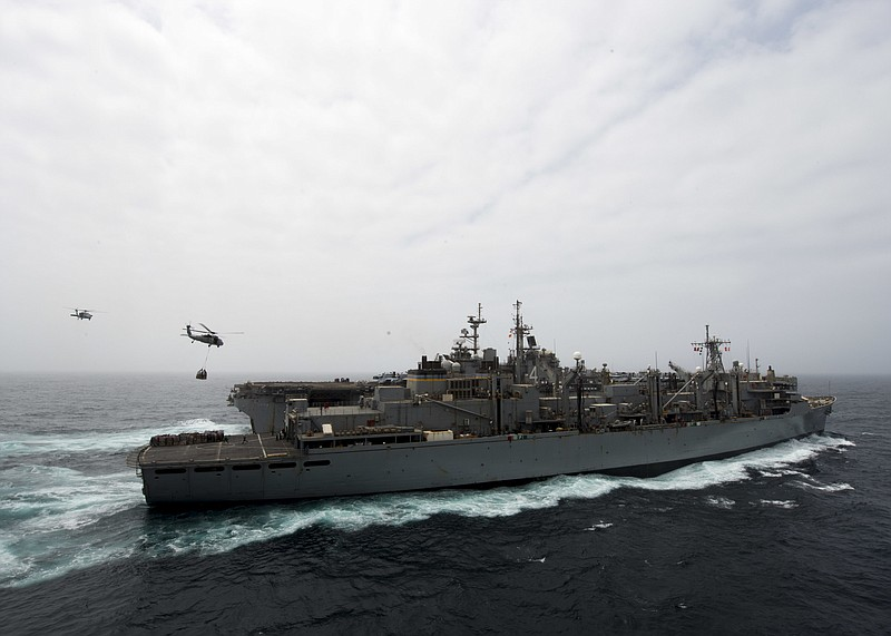 The amphibious assault ship USS Boxer, background, receives a vertical replen...