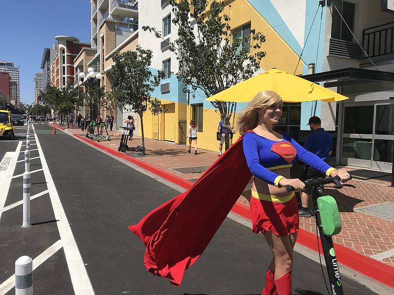 Comic-Con visitor Sapphire Nova rides an electric scooter down a protected bi...