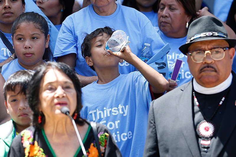 A young man sips some water as civil rights activist Dolores Huerta, left, sp...