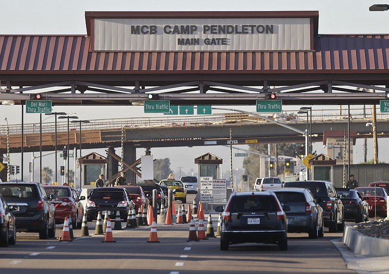 In this Nov. 13, 2013 file photo vehicles file through the main gate of Camp ...