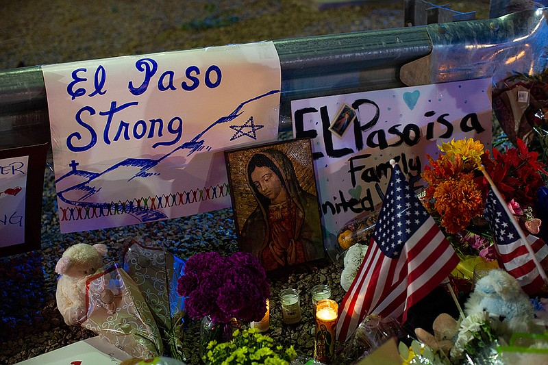 A Virgin Mary painting, flags and flowers adorn a makeshift memorial for the ...