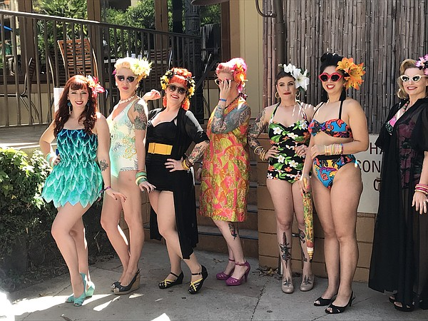 Tiki Oasis attendees pose for a photo in their swimsuits,...