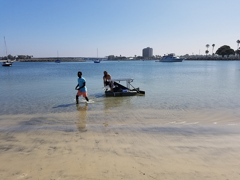 Engineering student Desmond Jones in the water of Mission Bay Point with FRED...