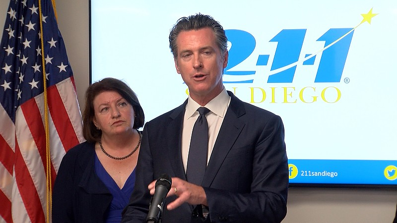Governor Gavin Newsom speaks at 211 San Diego, while standing in front of sta...