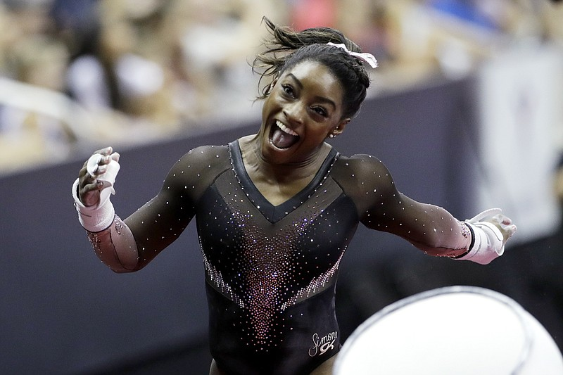 Simone Biles celebrates after competing in the uneven bars to win the all aro...