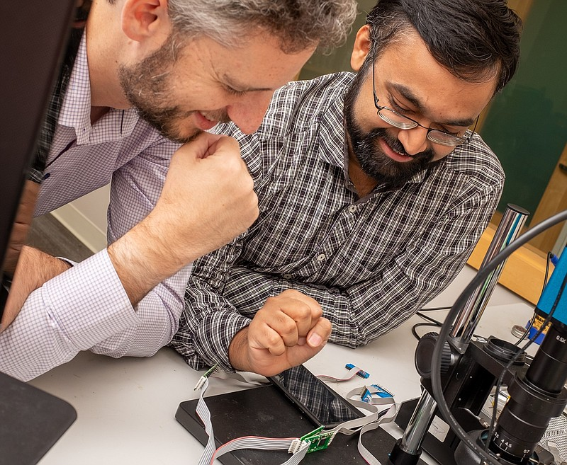UCSD engineers Nishant Bhaskar and Aaron Schulman look at skimmers taken from...