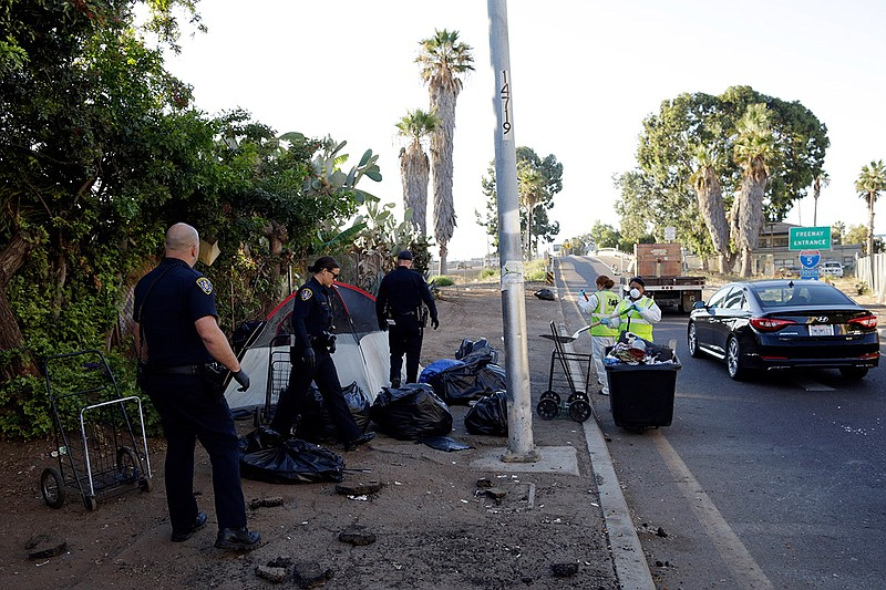 Police officers remove a tent left by the homeless during efforts to sanitize...