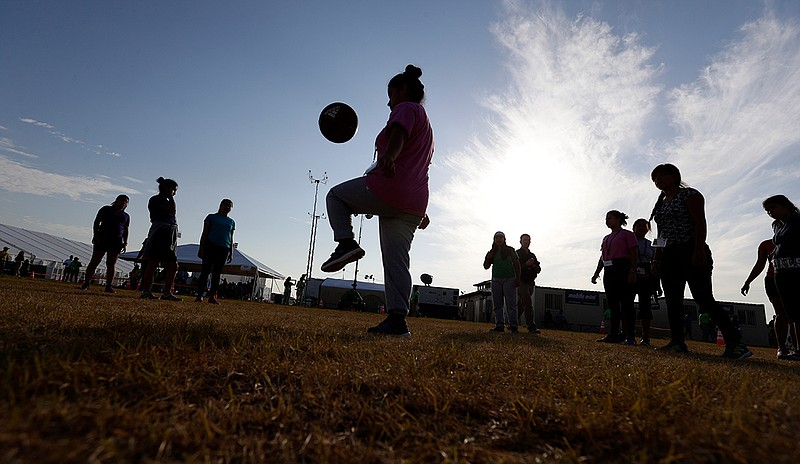 Immigrants play soccer at the U.S. government's newest holding center for mig...