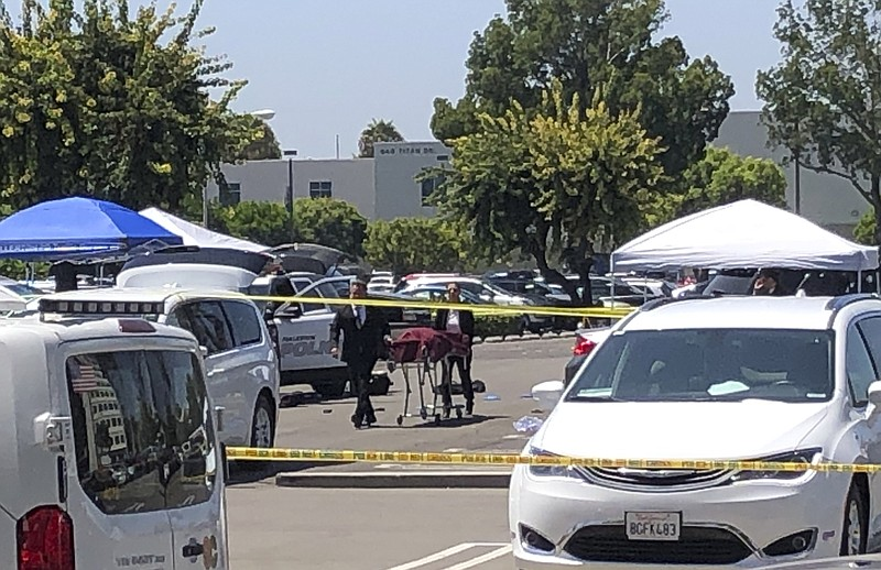 Orange County coroners remove a body of a stabbing victim from a parking lot ...