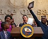 Gov. Gavin Newsom holds up the measure by Assem...
