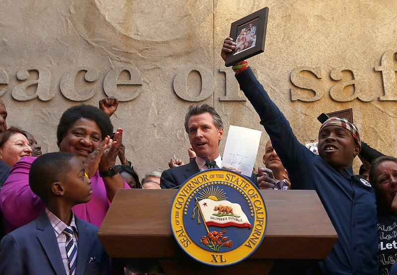 Gov. Gavin Newsom holds up the measure by Assemblywoman Shirley Weber, D-San ...