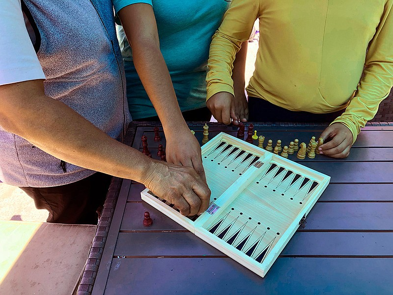 Luz Viviana Perez, 53, arranges chess board with her daughters, 17 and 12. at...