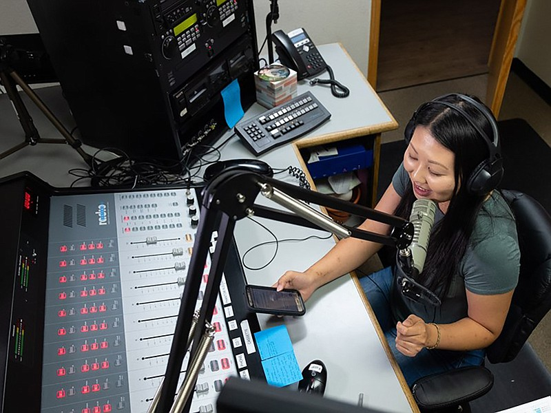 Vila Xiong operates the mixing board herself while hosting the