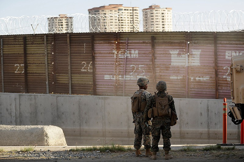 Marines look on during work to fortify the border structure that separates Ti...