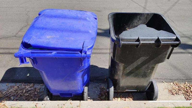 A broken San Diego trash can sits next to a recycling bin, September 5, 2019.