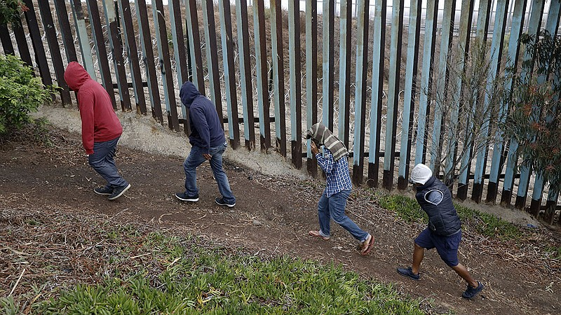 Central American migrants walk along the U.S. border fence looking for places...