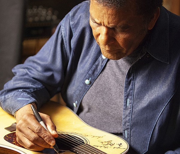 Charley Pride signs Martin D-28 guitar. Pride is among th...