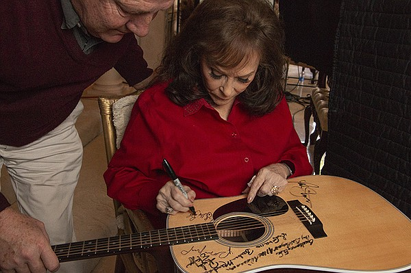 Loretta Lynn signs Martin D-28 guitar. Lynn is among the ...