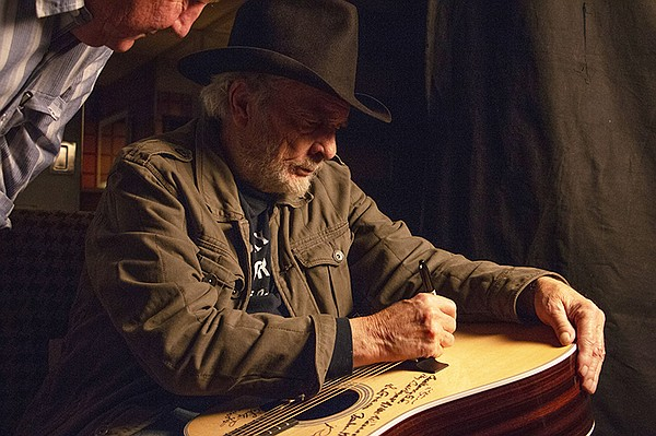 Merle Haggard signs Martin D-28 guitar. Haggard is among ...