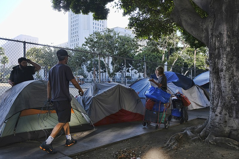 In this Monday, July 1, 2019 file photo, homeless people move their belonging...