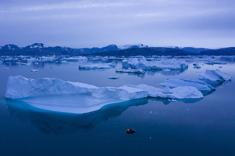 A boat navigates at night next to large icebergs near the town of Kulusuk, in...