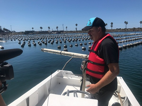 Matt Steinke prepares to lift up a buoy that marks the lo...