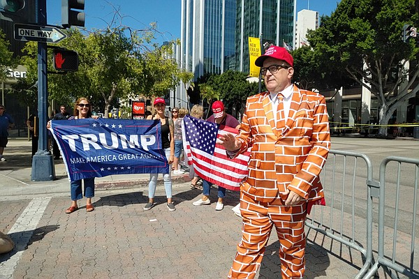 A man in a brick wall suit stands alongside other Trump s...