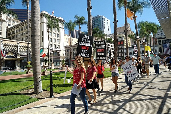 A group of anti-vaccine supporters walk in Horton Plaza P...