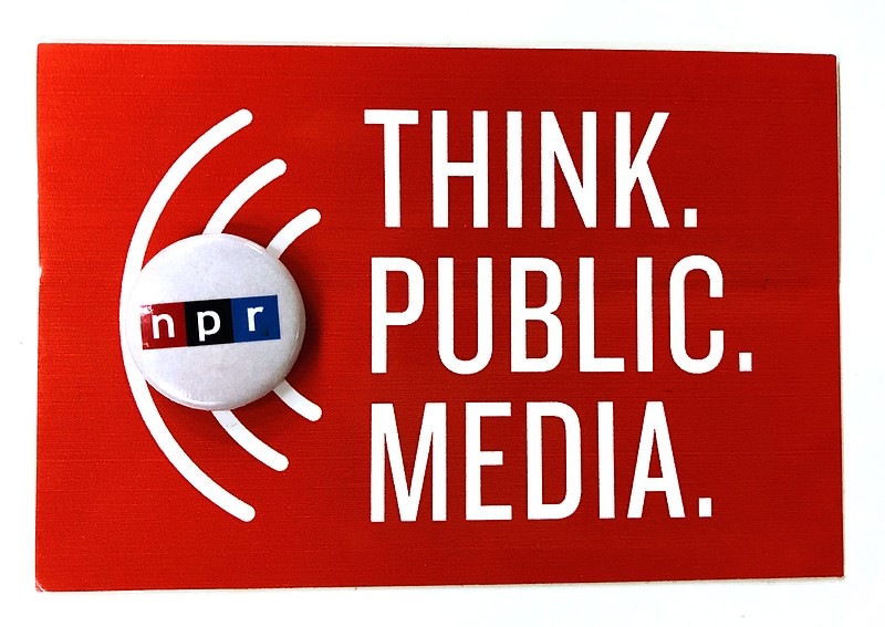 An NPR pin laying on top of a Think Public Media sign.