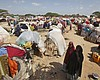 Newly displaced Somalis walk through a camp in ...