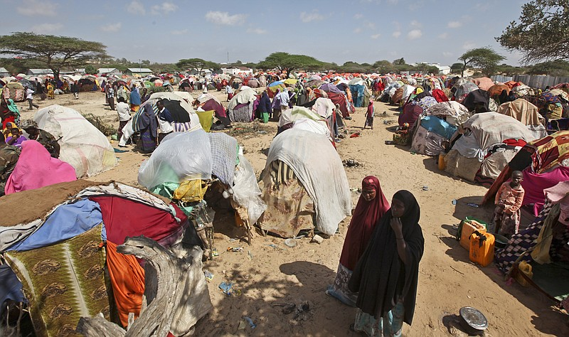 Newly displaced Somalis walk through a camp in the Garasbaley area on the out...