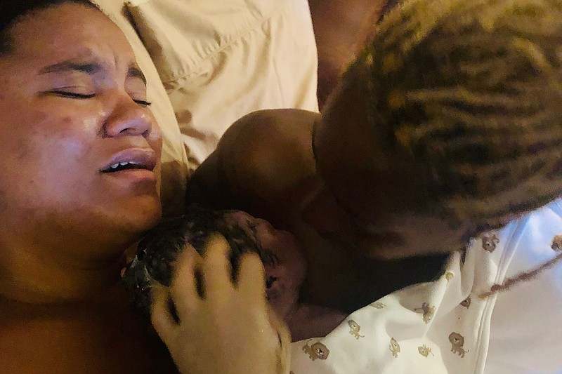 Sharavyn Johnson (left) lays as her wife, Nasira, holds their son Asir moment...