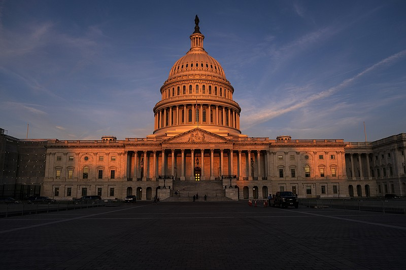 The rising sun divides the West Front of the U.S. Capitol in Washington, Wedn...