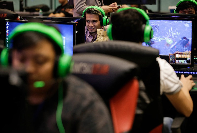 an esport (electronic sport) player smiles during the qualifying rounds for t...